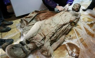 Macro mysterious mummy 700 years soaked in brown coffin